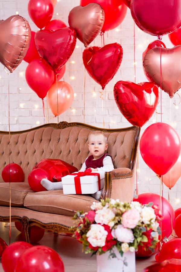 Концепция дня Валентайн - маленький ребенок с подарочной коробкой и красными в форме сердц воздушными шарами стоковые изображения rf