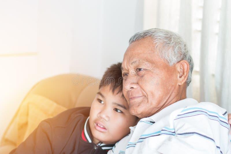 Концепция Дня отца и отца : Бабушка и племянник или внук азиатского происхождения. Мальчик обнимается, счастливо живя в доме стоковая фотография rf