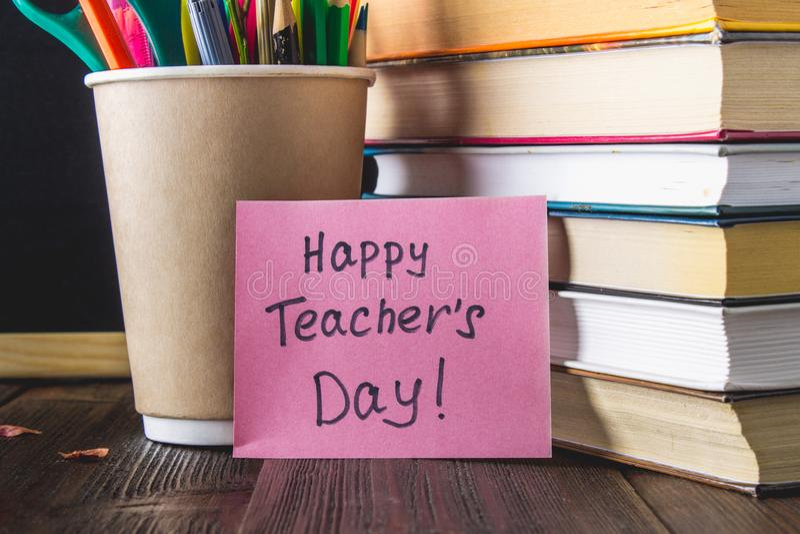 Концепция дня учителя Объекты на предпосылке доски Книги, зеленое яблоко, металлическая пластинка: День, карандаши и ручки счастл стоковое фото rf
