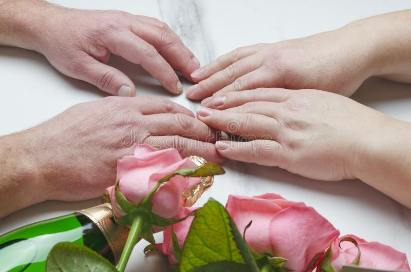 Концепция дня ` s валентинки St Пожилые пары имея дату Вино и цветки opf бутылки как подарок Съемка крупного плана стоковая фотография