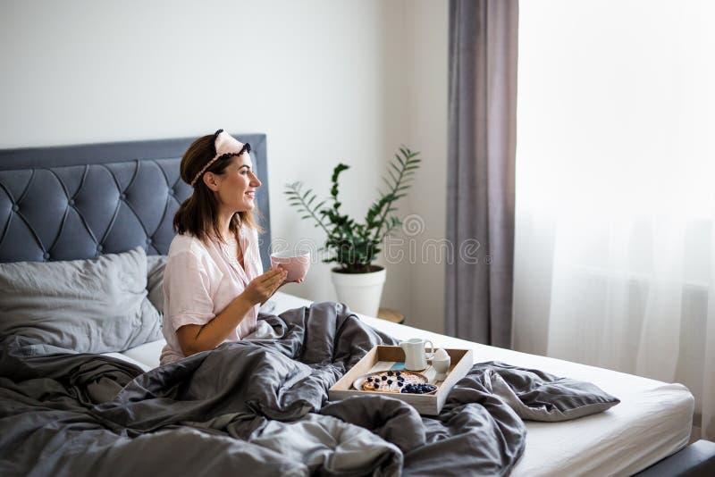 концепция доброе утро - портрет счастливой молодой красивой женщины в пижаме, сидящей на кровати и пьющей кофе стоковые фотографии rf