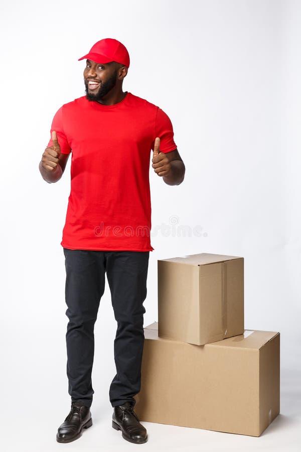 Концепция доставки - портрет счастливых Афро-американских пакетов коробки удерживания работника доставляющего покупки на дом и по стоковое фото