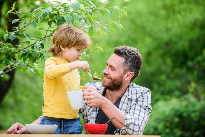 Концепция еды завтрака лета здоровая Сын отца съесть еду и иметь потеху Питаясь младенец Меню для детей Семья наслаждается стоковые изображения