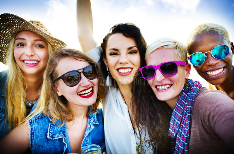 Концепция летних каникулов приятельства девушек усмехаясь совместно стоковая фотография