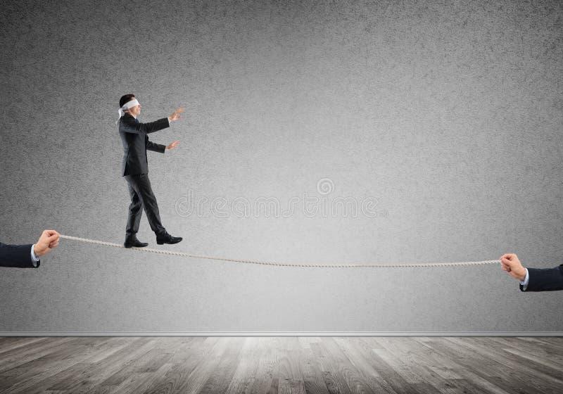 Концепция дела поддержки и помощи риска при человек балансируя на веревочке стоковые изображения