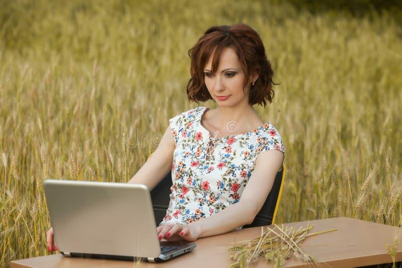 Концепция дела сняла красивой молодой женщины сидя на столе используя компьютер в поле стоковое фото rf
