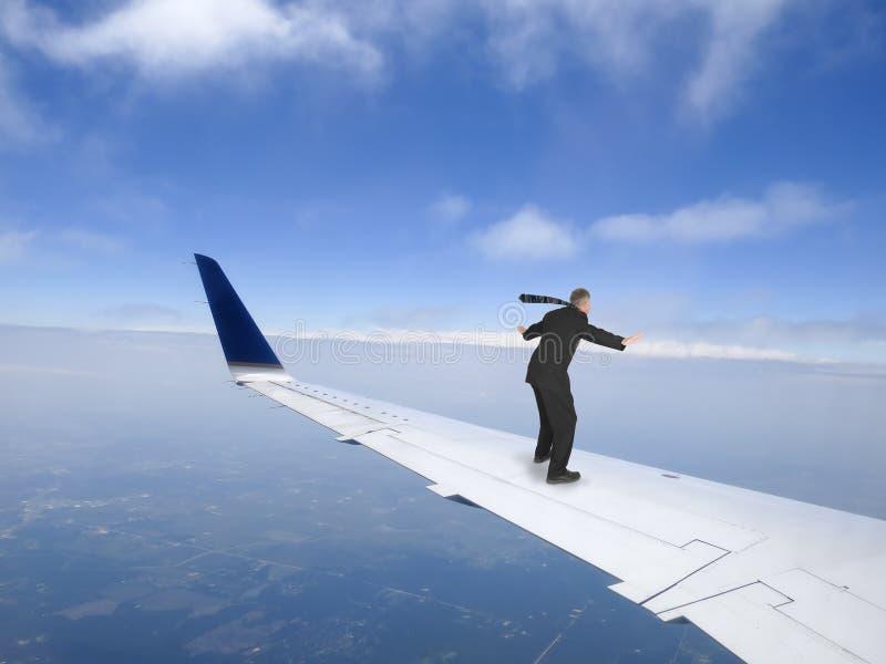 Концепция деловых поездок, летание на крыле реактивного самолета, отключение бизнесмена стоковое фото