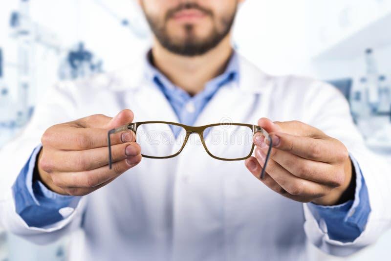 Концепция заботы зрения - optician давая новые оптически стекла стоковая фотография