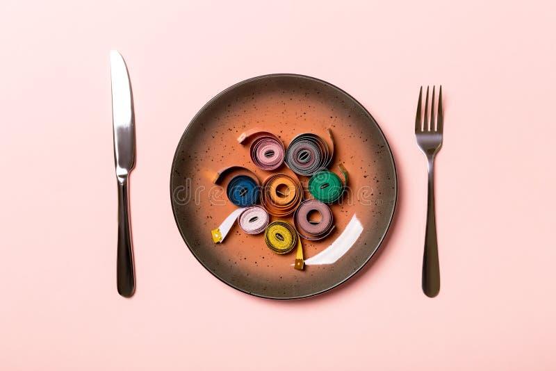 Концепция здорового питания плиты с измеряя лентой, вилкой и ножом на розовой предпосылке r стоковое фото