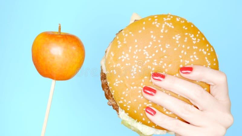 Концепция здоровой и нездоровой еды Yaloko против гамбургеров на яркой голубой предпосылке женские руки с красным ногтем стоковое фото rf