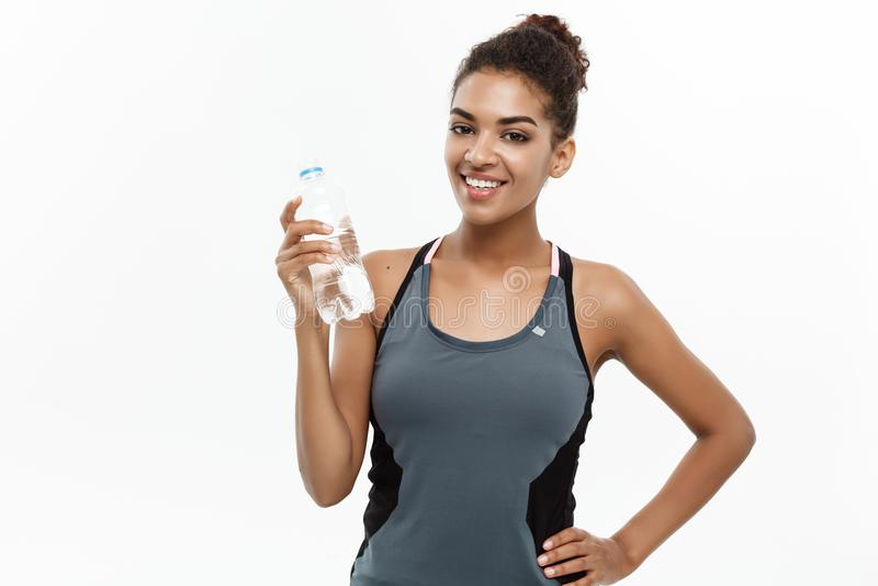 Концепция здоровых и фитнеса - красивая Афро-американская девушка в спорте одевает держать пластичную бутылку с водой позже стоковое фото rf