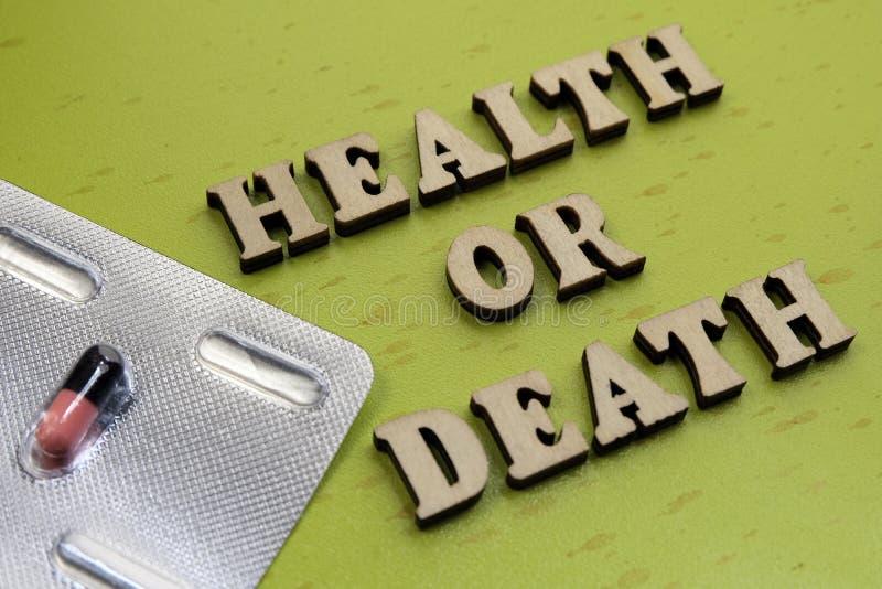 Концепция здоровья или смерти Надпись деревянных писем рядом с таблеткой на зеленой предпосылке стоковое изображение rf