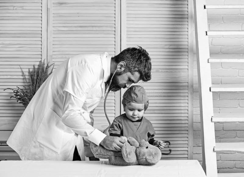 Концепция здравоохранения и детства Стетоскоп владением человека и мальчика стоковые изображения