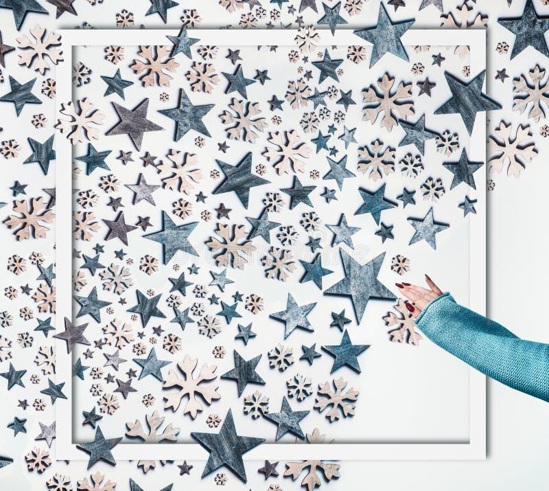 Концепция зимних праздников Женщина, протягивающая руку в трикотаже, делает голубыми звездами и декоративно-снежиновые композиции стоковые фотографии rf