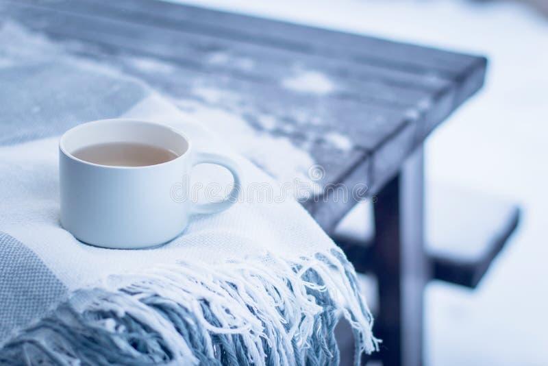 Концепция зимы, деревянный стол покрытый со снегом в задворк или парке, уютное одеяло и чашка горячего чая outdoors стоковые изображения