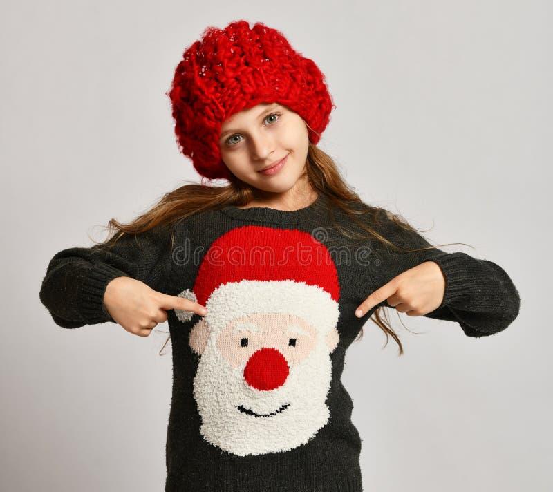 Концепция зимы рождества - усмехаясь ребенк маленькой девочки указывая пальцы на усмехаться красной шляпы x-mas Санта Клауса счас стоковые изображения rf