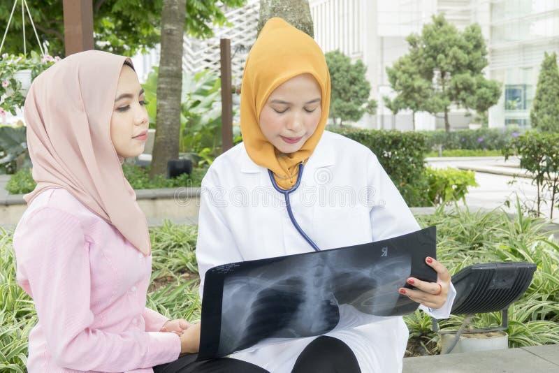 Концепция здравоохранения, медицинских и радиологии - милые доктора смотря компьтер-книжку стоковое фото rf