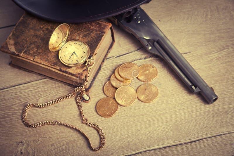 Концепция играть в азартные игры и злодеяния с золотыми монетками и оружием стоковое фото rf