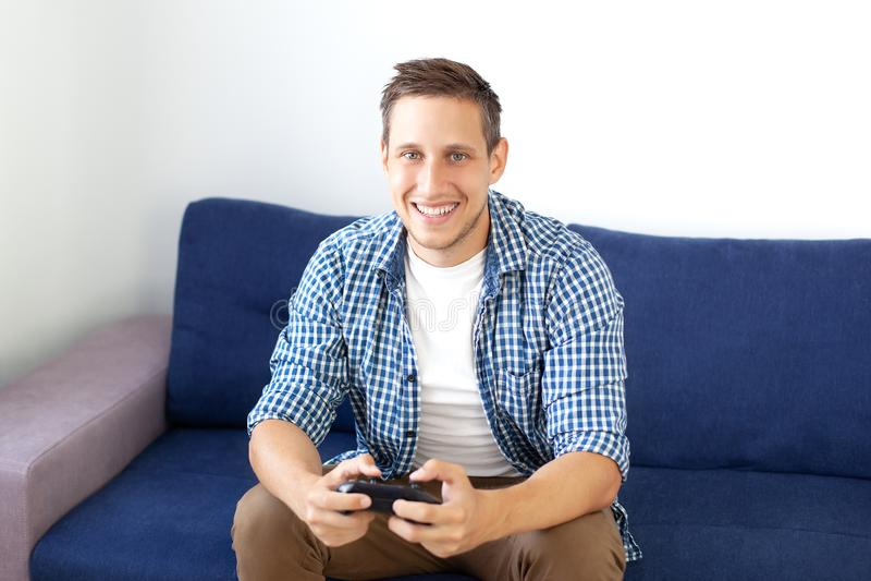 Концепция игры парень играет видеоигру с кнюппелем дома Усмехаясь человек в рубашке, сидя на кресле, стоковое изображение rf