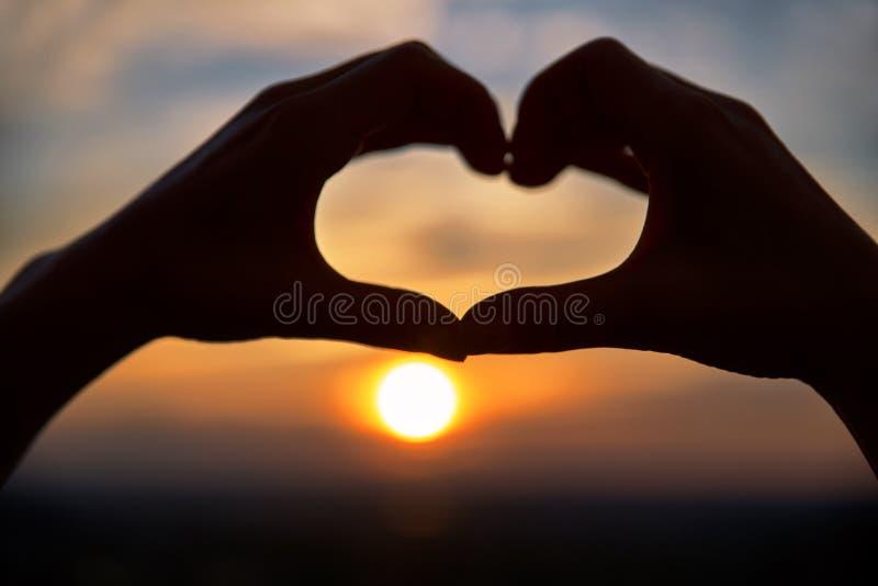 Концепция или схематические руки женщины в любов, символе сердца над предпосылкой Монреаля Форма сердца делая из рук против стоковые изображения rf
