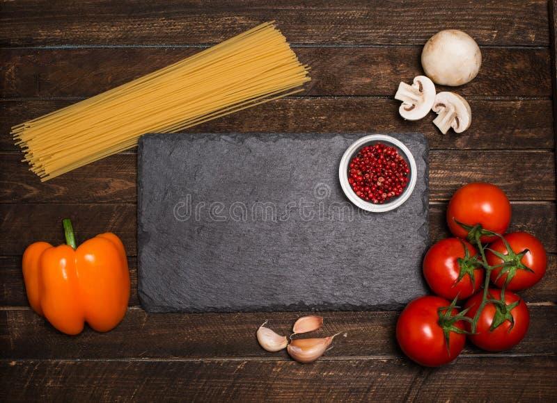 Концепция ингридиентов соуса для пасты на черной осмотренной предпосылке шифера стоковые фотографии rf