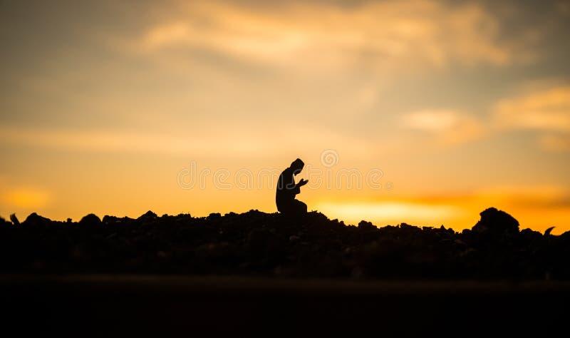 Концепция ислама вероисповедания Силуэт человека моля на предпосылке мечети на заходе солнца стоковое фото