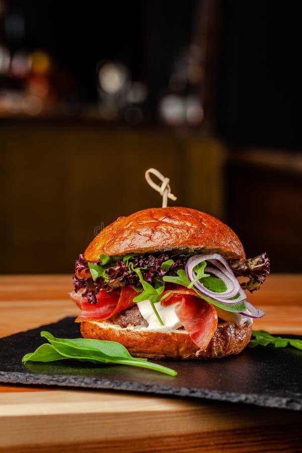 Концепция итальянской домашней кухни Бургер с котлетой мяса говядины и свинины, сыром моццареллы, сосиской салями, Пармой, arugul стоковая фотография rf
