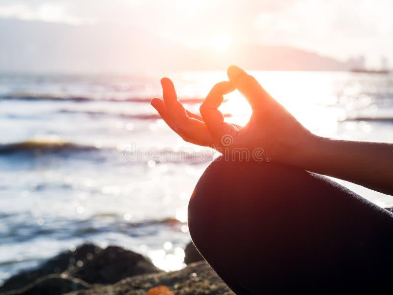 Концепция йоги Представление лотоса руки женщины крупного плана практикуя на пляж на заходе солнца стоковые фото