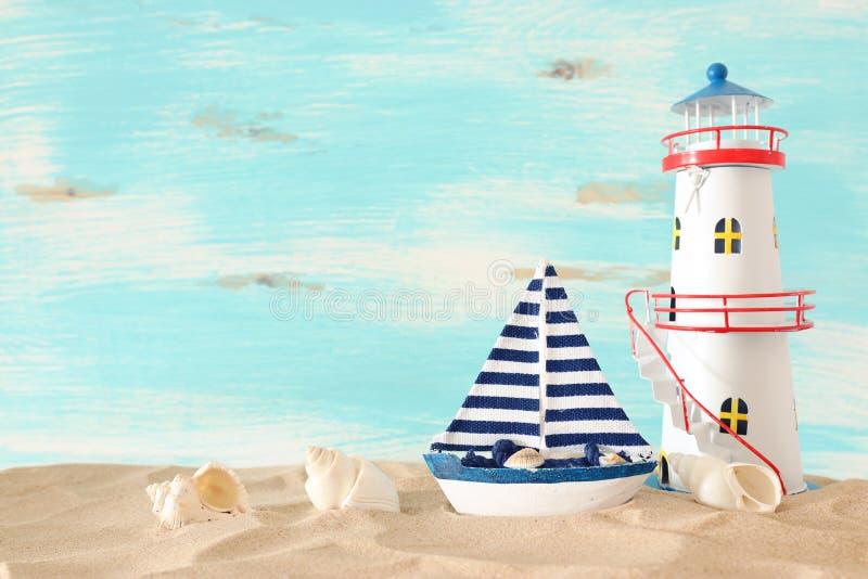 Концепция каникул и лета с винтажной шлюпкой, морскими звёздами, маяком и seashells над песком пляжа перед пастельной синью стоковые изображения rf