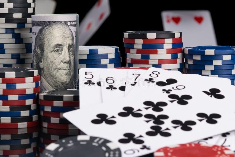Концепция карт и обломоков покера с деньгами на темной предпосылке стоковое фото