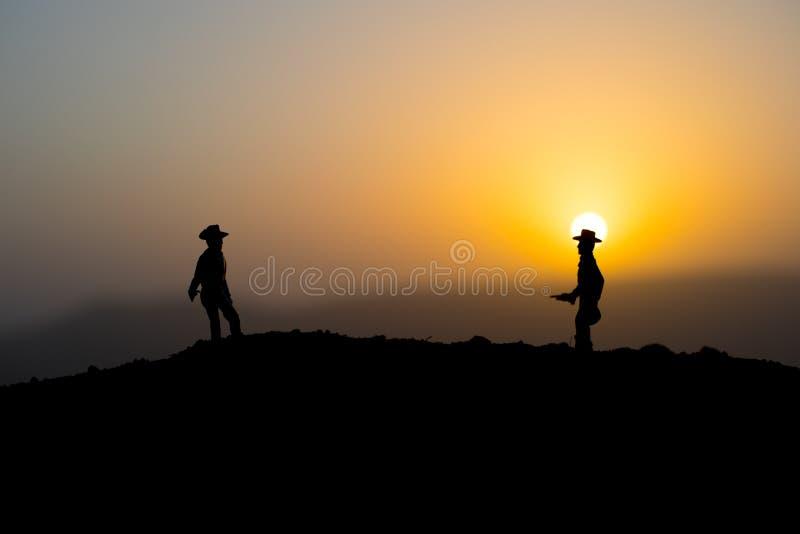 Концепция ковбоя Силуэт ковбоев на времени захода солнца Силуэт ковбоя на горе с желтым небом стоковое фото