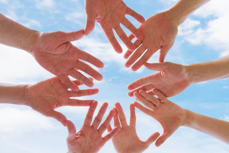 Концепция команды или братства, группа людей кладя руки совместно стоковые фотографии rf