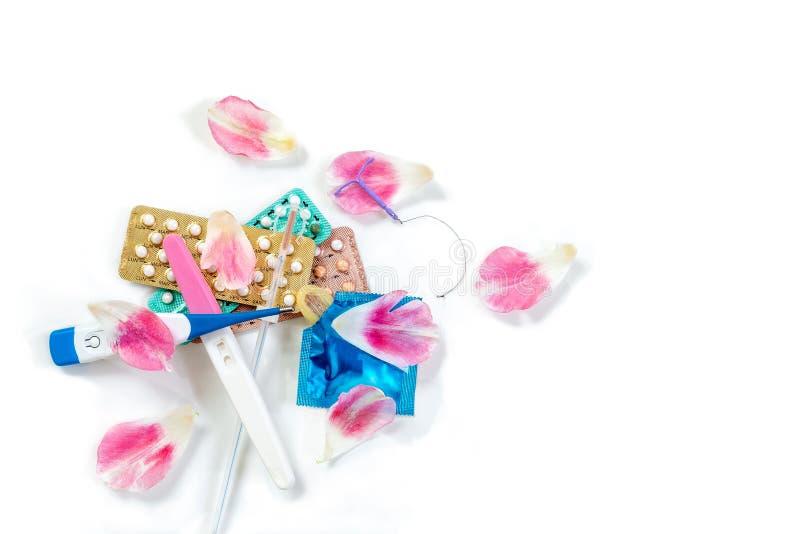 Концепция контрацепции - несколько печатают метода регулирования рождаемости на белой предпосылке с лепестками цветков стоковые изображения rf