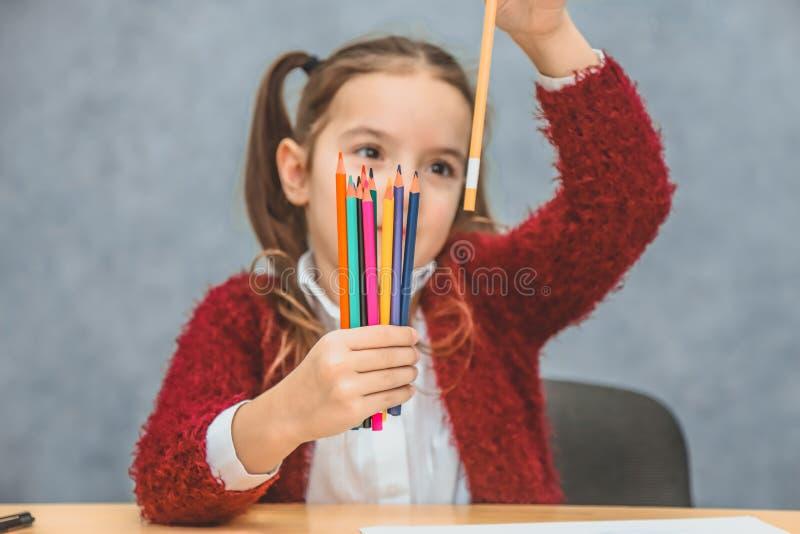 Концепция конца-вверх покрашенных карандашей в девушках одной руки Держит черный карандаш, смотрит его Серая предпосылка _ стоковые фото