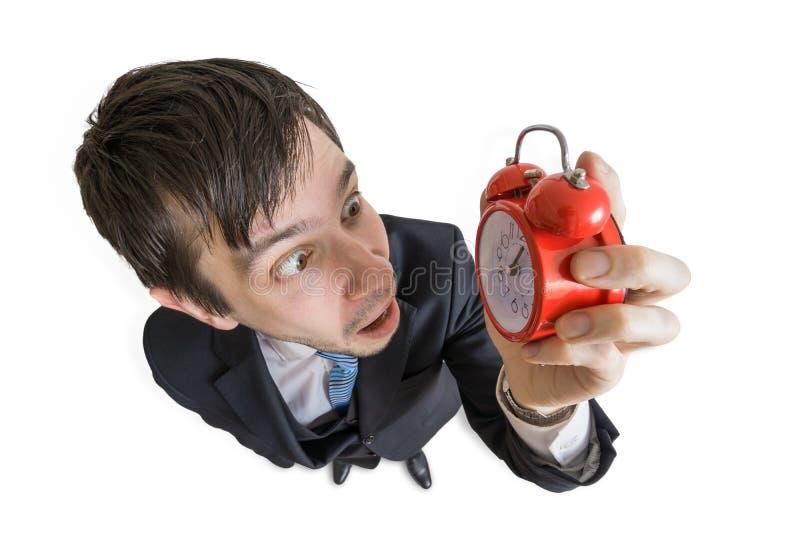 Концепция крайнего срока Молодой человек смотрит на часах и сотрясен над взглядом белизна изолированная предпосылкой стоковая фотография rf