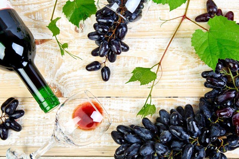 Концепция красного вина с бутылкой, стеклом и виноградинами стоковая фотография rf
