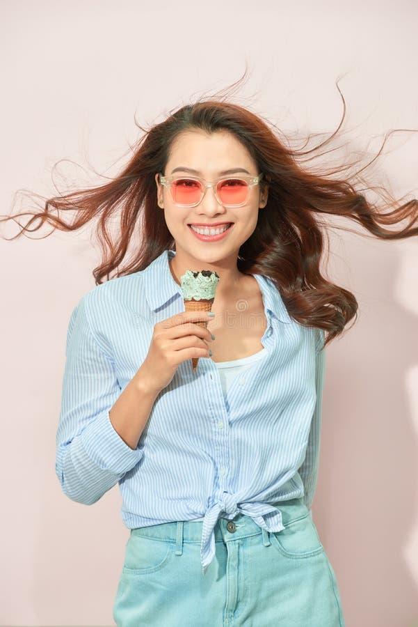 Концепция лета, высококалорийной вредной пищи и людей - молодая женщина или девочка-подросток в солнечных очках есть мороженое стоковое изображение