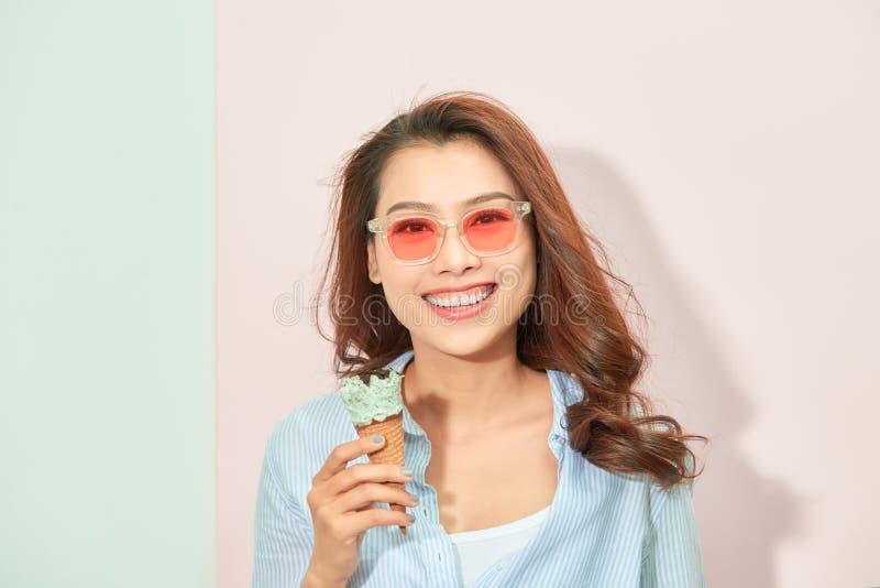 Концепция лета, высококалорийной вредной пищи и людей - молодая женщина или девочка-подросток в солнечных очках есть мороженое стоковое изображение rf