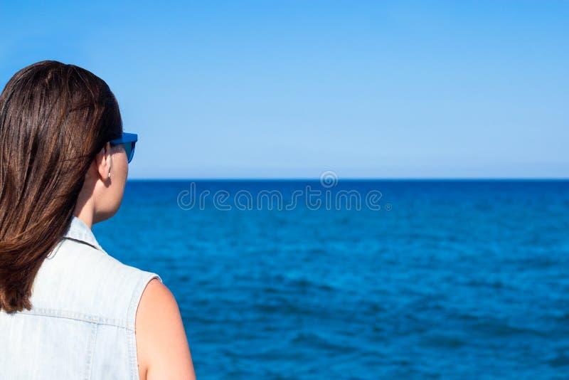 Концепция лета и каникул - задний взгляд молодой женщины над beac стоковая фотография