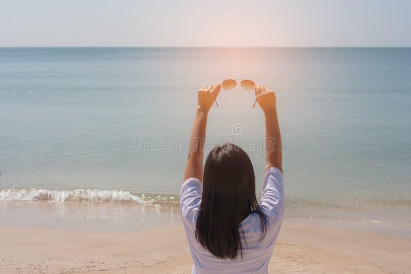 Концепция летних каникулов и праздника: Женщина стоя на пляже песка Она держа солнечные очки в ее руке стоковые изображения rf