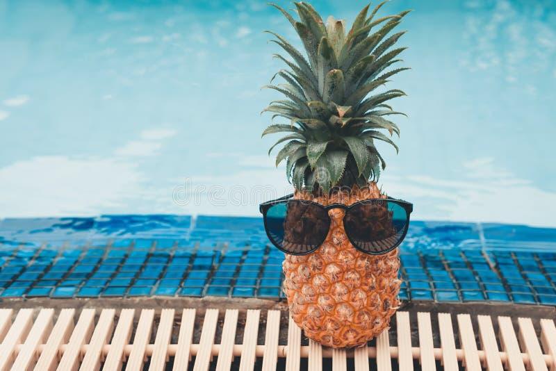 Концепция летних каникулов, солнечные очки ананаса нося около бассейна стоковое изображение