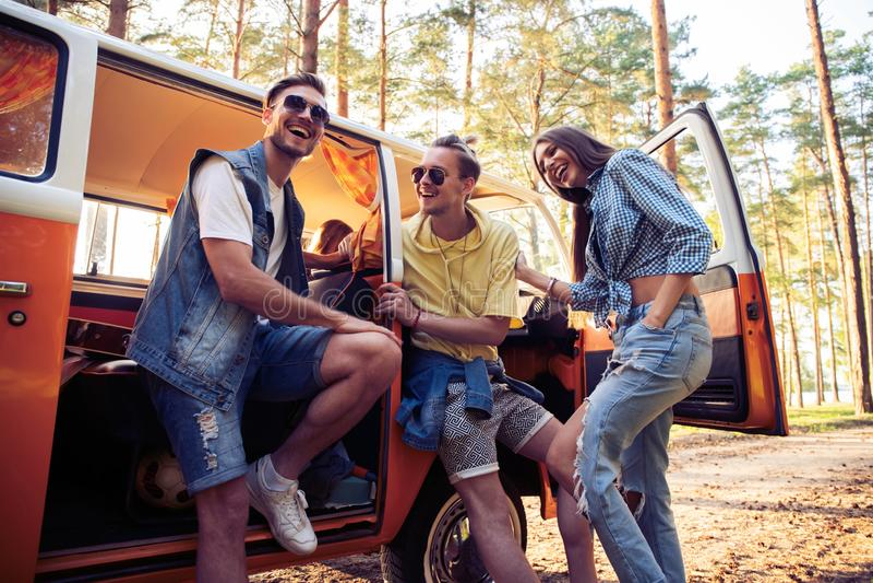 Концепция летних отпусков, поездки, каникул, перемещения и людей - усмехаясь молодые друзья hippie имея потеху над минифургоном стоковые изображения