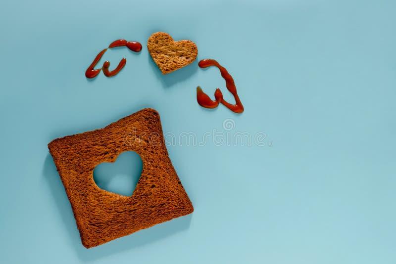 Концепция любов и свободы Плоское положение отрезанного провозглашанного тост хлеба в форме сердца и крыльев нарисованных томатны стоковые изображения