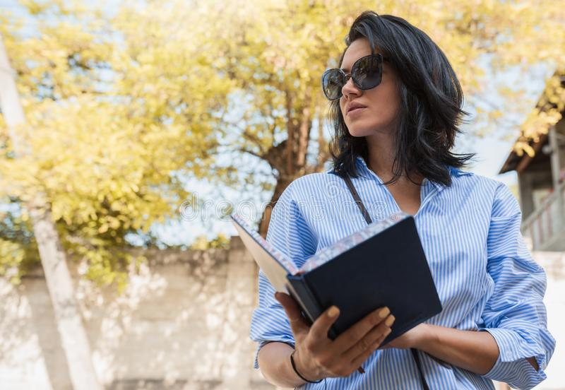 Концепция людей, дела и работы Жизнерадостное женское enterpreneur использует блокнот, workes на открытом воздухе, планируя ее де стоковые изображения