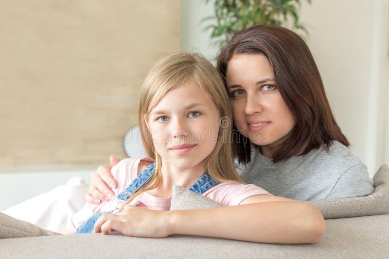 Концепция людей и семьи - счастливая усмехаясь девушка с матерью обнимая на софе дома стоковые фотографии rf