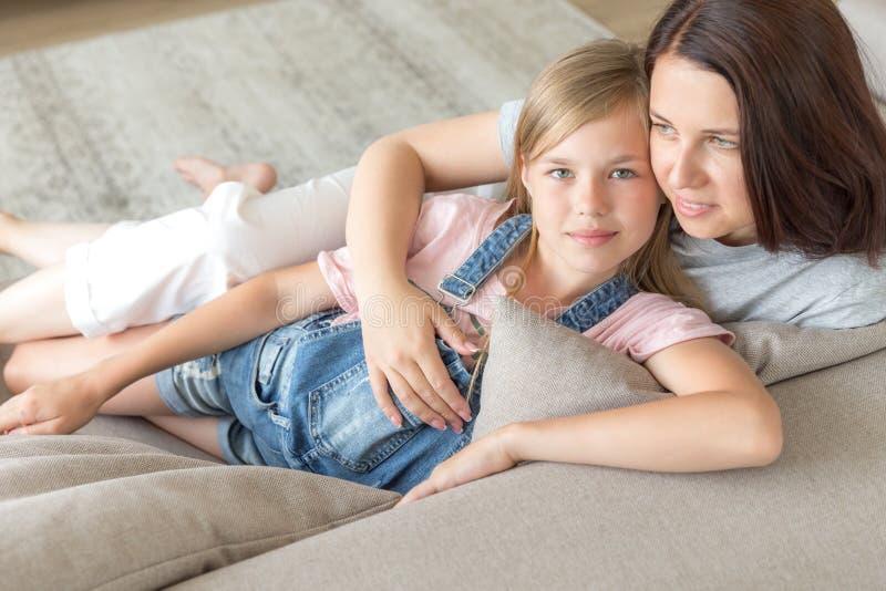 Концепция людей и семьи - счастливая усмехаясь девушка с матерью обнимая на софе дома стоковое фото