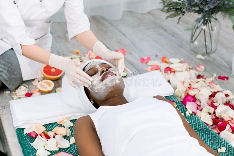 Концепция людей, красоты, спа, косметологии и skincare - конец вверх красивой молодой африканской женщины лежа с закрытыми глазам стоковая фотография
