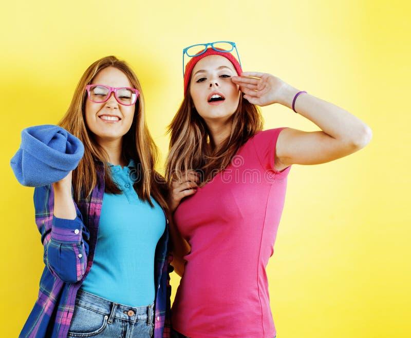 Концепция людей образа жизни: 2 довольно молодых девочка-подростка школы имея усмехаться потехи счастливый на желтой предпосылке стоковые изображения rf