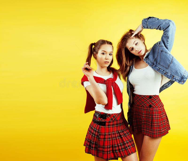 Концепция людей образа жизни: 2 довольно молодых девочка-подростка школы имея усмехаться потехи счастливый на желтой предпосылке стоковое фото