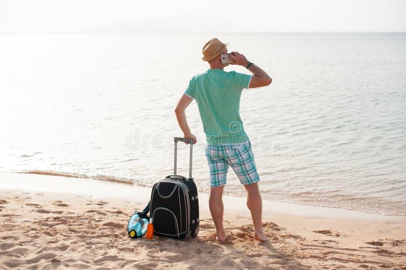 Концепция людей перемещения природы - положение человека около моря на пляже с чемоданом и говорить по телефону стоковое изображение